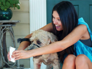 Woman showing her dog something on her phone
